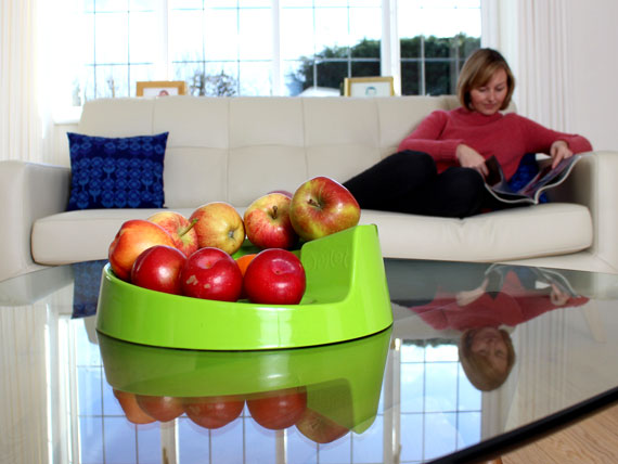 A green Rollabowl filled with fruit on the coffee table