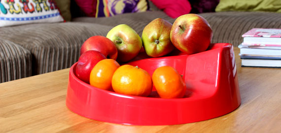 A Red Rollabowl fruit bowl on a coffee table.
